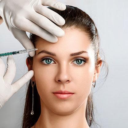 Mit einer feinen Nadel wird das Botulinum in die Stirnfalte einer jungen Frau gespritzt